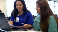 Hispanic female professor of nursing tutoring young adult college student