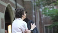 hispanic graduate with diploma with mother  Richmond, Virginia, USA