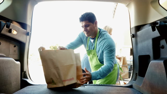 Hispanic grocery store employee is helping mother and daughter load grocery bags in SUV or minivan