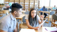 Hispanic high school girl tutoring male African American classmate in library
