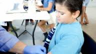 Hispanic little boy getting flu shot at outdoor community health fair