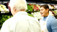 Hispanic mid-adult male grocery store employee is assisting senior Caucasian male customer in produce section of grocery store