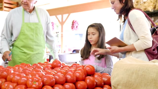 Hispanische Mutter zeigt junge Tochter über Sie Tomaten in produzieren Markt