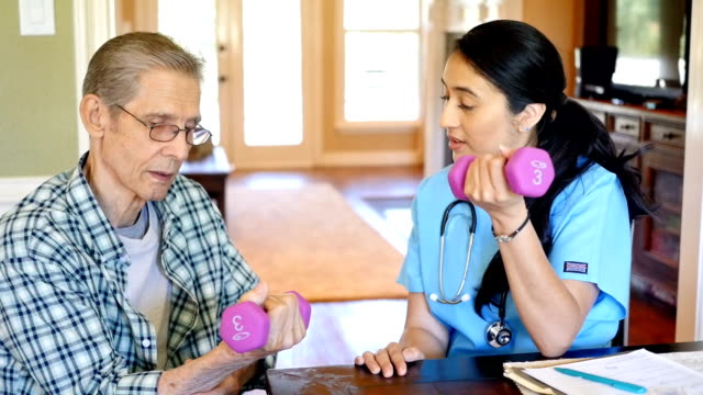 Hispanic nurse helps senior patient with hand weights during home visit