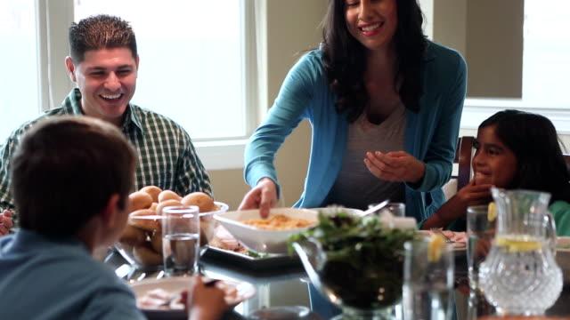 Hispanic genitori avendo pasto con i figli al tavolo da cena a casa
