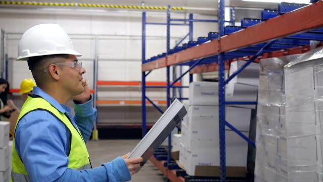 Hispanic warehouse manager spricht am Telefon an Kunden