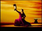 Hispanic woman in native dress with fan flamenco dancing in studio with backdrop