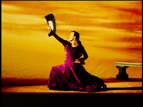 Hispanic woman in native dress with fan flamenco dancing in studio with backdrop