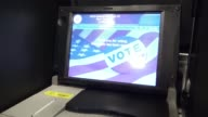 Hispanic woman inserting voting ballot into electronic voting machine during the US General Presidential Election /Upper West Side PS 163 West 96th...