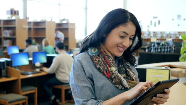 Hispanic woman is using digital tablet in library, looks up and smiles at camera