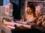 Hispanic woman + senior woman looking at documents at desk at home + using adding machine
