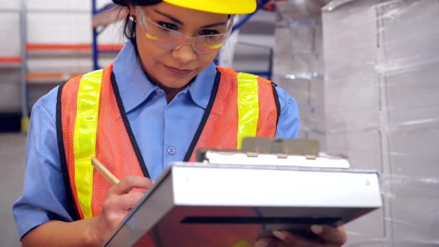 Hispanic woman writing with clipboard in shipping distribution warehouse