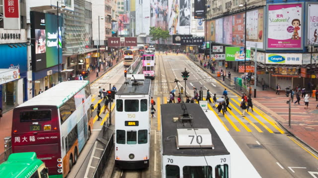 Historic trams and people crossing road in central Hong Kong