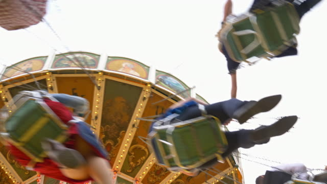 historic vintage chain swing carousel on the 'Oide Wiesn', unrecognisable blurred spinning people seen from below