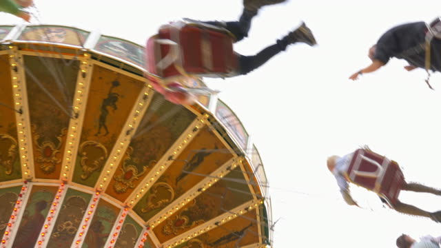 historic vintage chain swing carousel on the 'Oide Wiesn', unrecognisable blurred people spinning