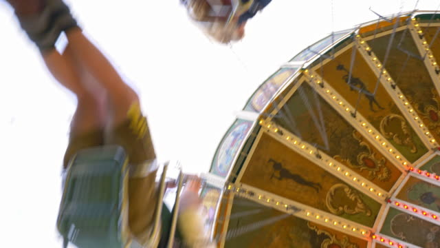 historic vintage chain swing carousel on the 'Oide Wiesn', unrecognisable blurred people spinning seen from below