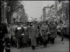 Hitler Goering and military entourage walk down street lined with Swastika flags / Sudetenland Czechoslovakia