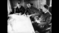 Hitler sitting at table with other Nazis discussing war strategy / animated map with Nazi swastika symbol showing conquered territories of France...