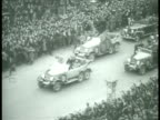 Hitler's motorcade w/ people lining street w/ Hitler standing in front car saluting passing crowds lining road