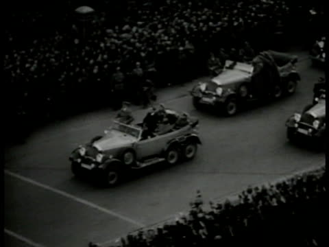 Hitler's motorcade w/ people lining street w/ Hitler standing in front car saluting passing crowds lining road WWII