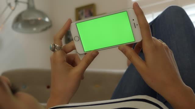 Håller smartphone med chromakey skärm. Kvinna liggande inomhus tittar på hennes telefon.