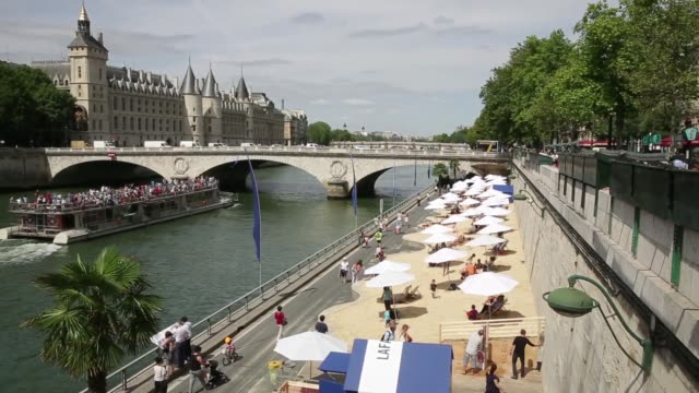 Holidaymakers sit under parasols on the ParisPlage artificial beaches along the River Seine in Paris France on Wednesday July 22 2015 Shots...