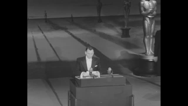 WS Academny Awards orchestra and stage / Oscars on table / WS audience / Frank Sinatra at podium announces Eva Marie Saint in New York winner...