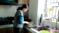 Home cooking: a senior woman cutting vegetables