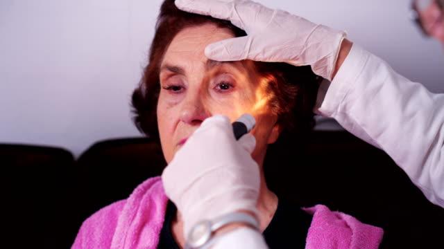 Hem hälso-läkare kontrollerar ögat reflexen av äldre patient