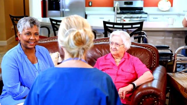 Home healthcare nurse evaluates senior adult patients at nursing home.