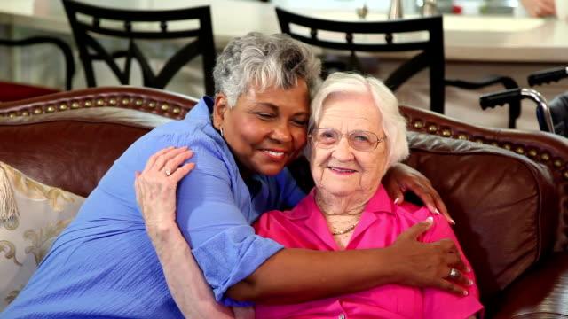Home healthcare Krankenschwester mit einem senior erwachsenen Patienten. Hugs.