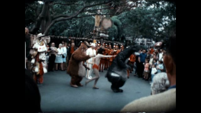 Home movie of live performers doing a dance routine from the Jungle Book at a Disneyland Parade in the 1960's