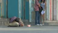 MS Homeless man lying on ground checking cup of money / Ningbo, Zhejiang, China