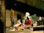 Homeless people sleeping in rundown part of city with political graffiti on walls Sao Paulo