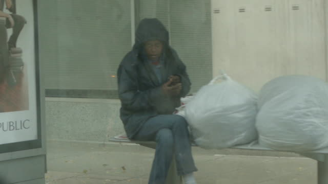 Homeless woman takes shelter in a bus stop on October 29 2012 in Washington DC