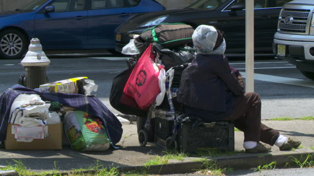 A homeless women sits with her stuff on a corner street in Manhattan