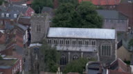 Homes crowd a church with a Norman tower in England. Available in HD.