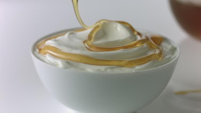 Honey dipper drizzles honey over yogurt