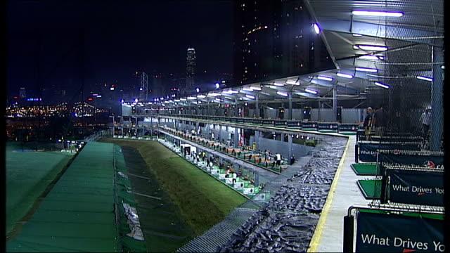 Golf driving range CHINA Hong Kong General views of golfers hitting balls in outdoor golf driving range illuminates skyscrapers in background