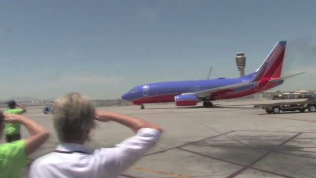 MS of Honor Flight Arizona volunteers as they salute goodbye to Honor Flight vets on plane before takeoff
