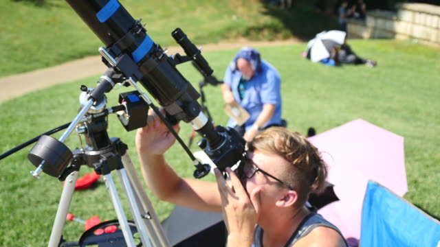 An amateur astronomer lines up his telescope before the beginning of the eclipse at Little River Park before the moon begins to block the sun during...
