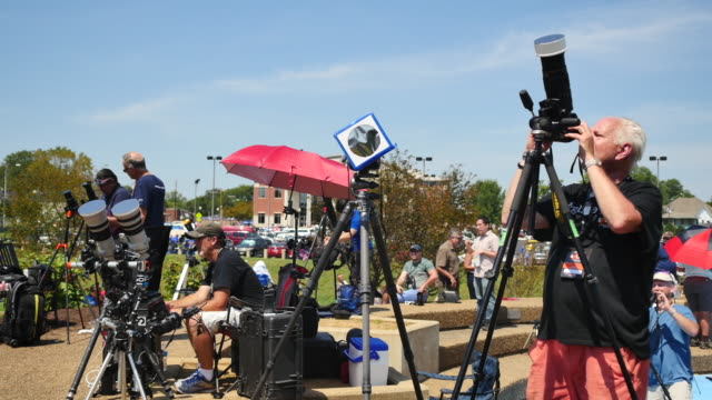 Eclipse watchers view a total solar eclipse's transit across the United States during the Great American Eclipse August 21 2017 at Little River Park...
