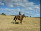 Horse and rider gallop over South African plain