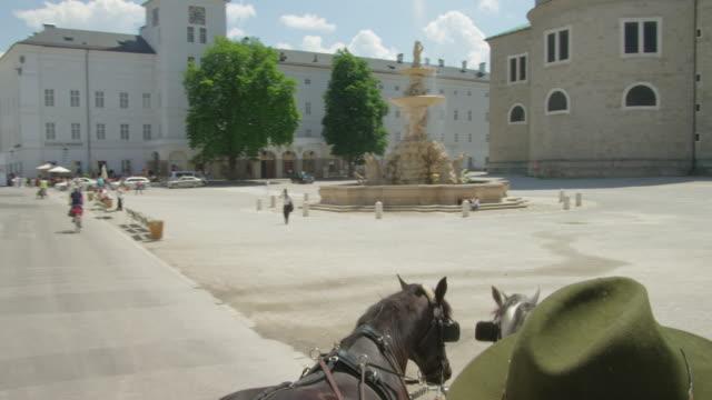 POV WS horse drawn carriage moving through the historic center of Salzburg, crossing Residenzplatz (Residence Square)
