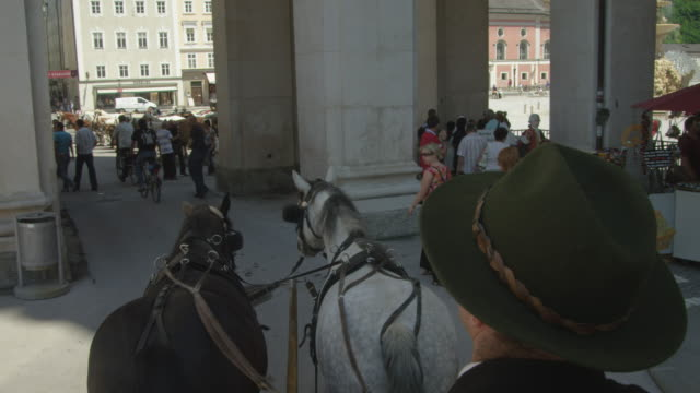 POV WS horse drawn carriage moving through the historic center of Salzburg, leaving the Domplatz (cathedral square) and entering Residenzplatz (Residence Square)