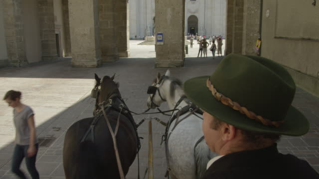 POV WS horse drawn carriage moving through the historic center of Salzburg, entering cathedral square through one of the arches, TU to cathedral