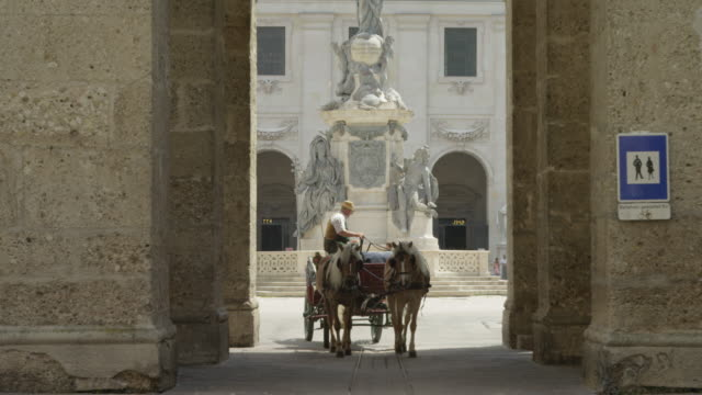 LS horse drawn carriage moving to camera through one of the arches leading to the Domplatz (cathedral square)