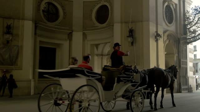 Horse drawn carriage riding away from camera through Roman arch,Michaelerplatz.Pan L to R.Medium shot.