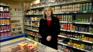Horse meat scandal continues INT Findus food products in shop freezer with hand removing 'Findus Macaroni Cheese'' Reporter to camera