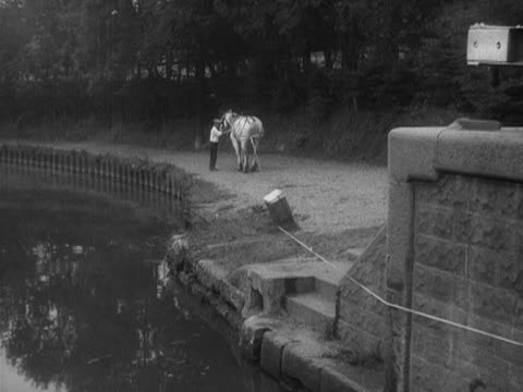 A horse pulls a barge along a canal